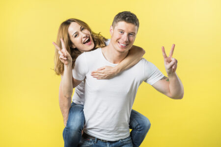 Smiling man carrying wife piggyback ride making victory sign