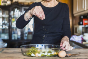 Woman adding salt to food
